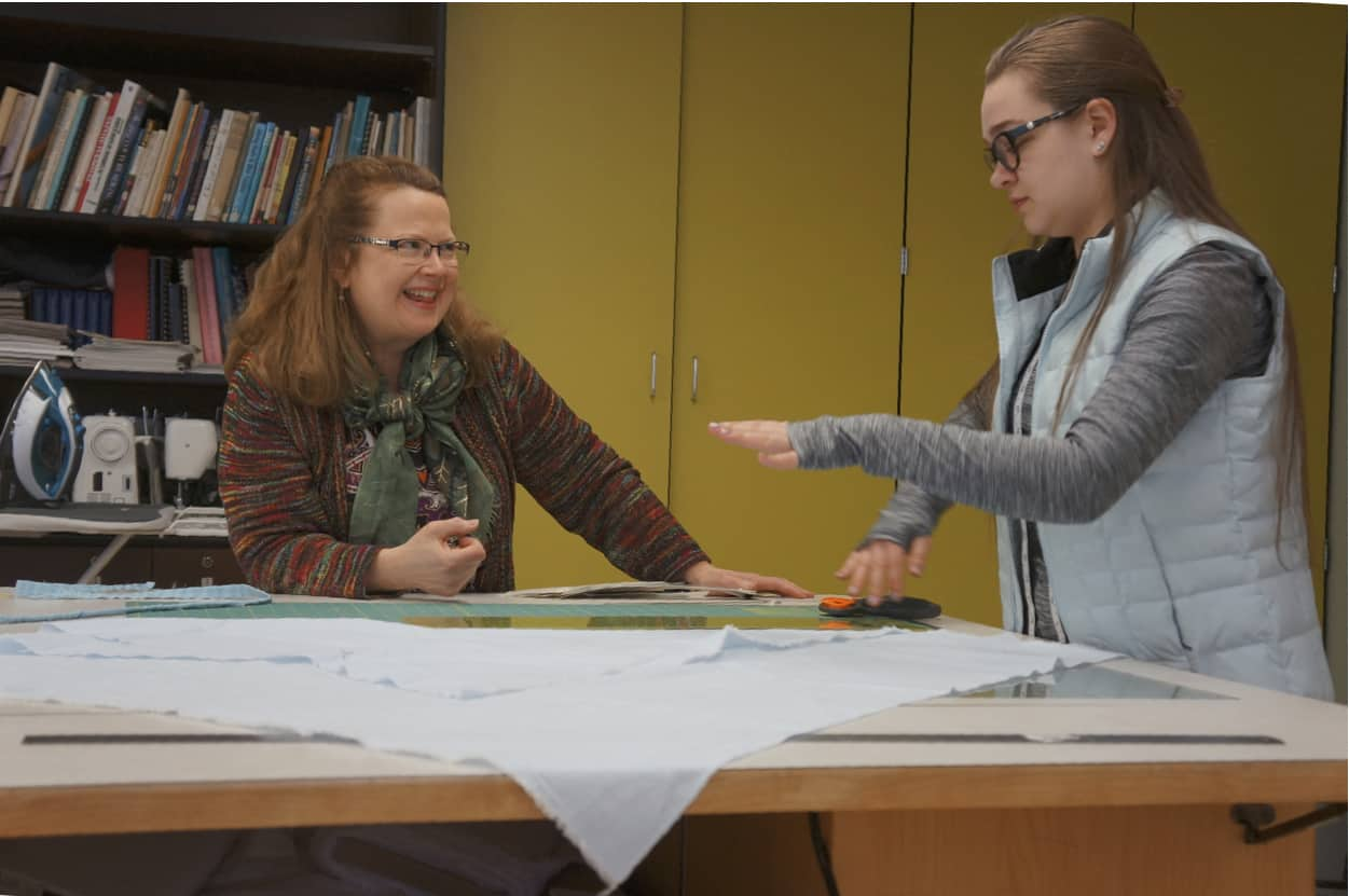 professor ann braaten assists student with designs